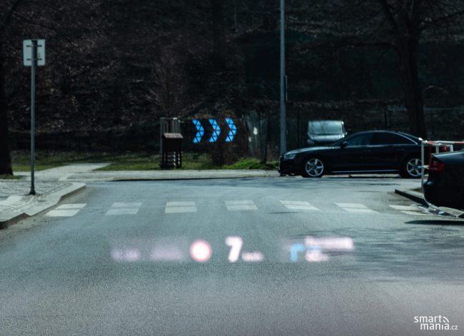 Modré šipky ukazují, kam má řidič odbočit. Jsou vzdálené daleko před řidičem, není tedy možné na ně zaostřit a mít zároveň ostré ostatní informace head-up displeje.